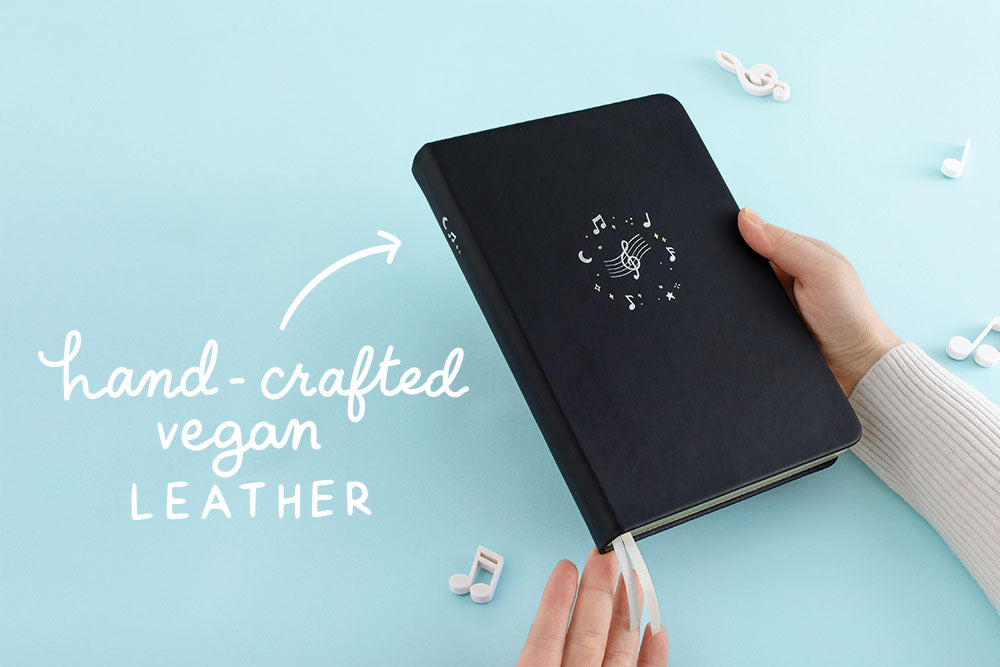 Tsuki Lunar Notes bullet journal in hands with hand-crafted vegan leather doodle images in blue background