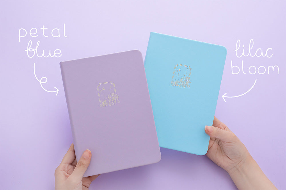 Tsuki Endless Summer Limited Edition Bullet Journals in Lilac Bloom and Petal Blue held in hands in lilac background