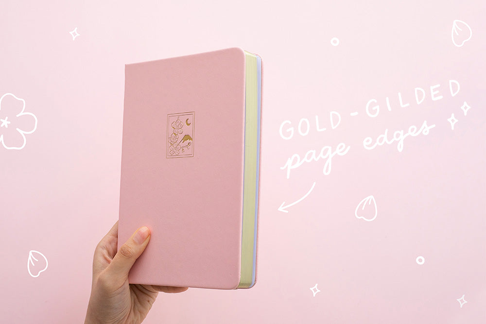 Petal pink bullet journal notebook cover and gold gilded page edges on a pink background