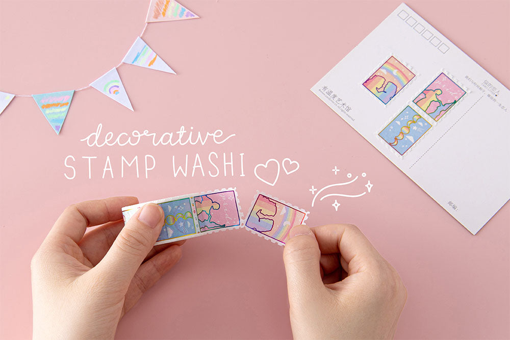 Tsuki Rainbow Pride Washi Tape with decorative stamps held in hands with postcard and bunting on light pink background