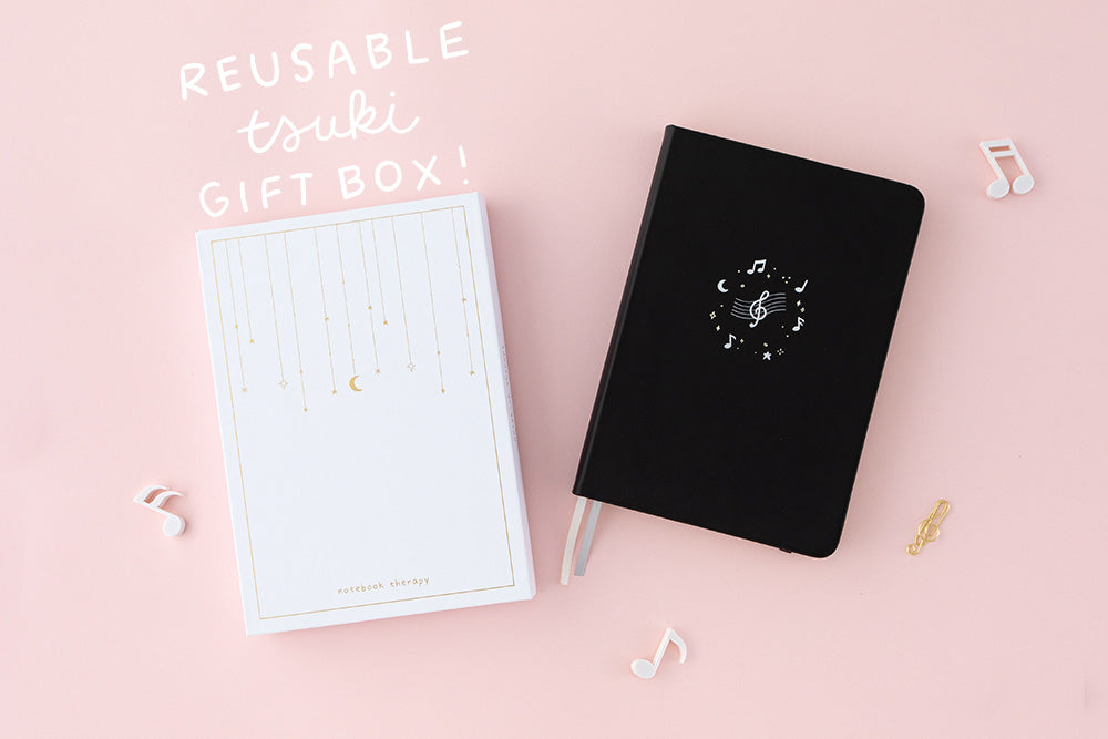 Tsuki Lunar Notes bullet journal with box packaging flat lay with reusable tsuki gift box doodle image on pink background