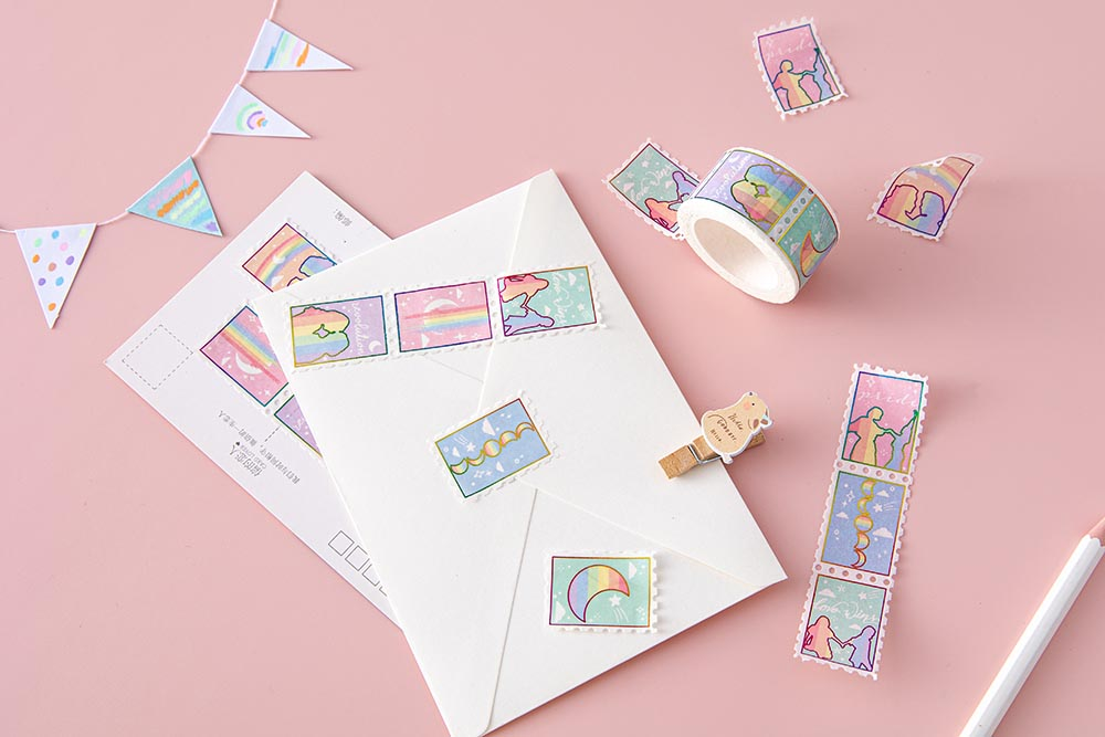 Tsuki Rainbow Pride Washi Tape on letter envelope with postcard and pencil and wooden bear peg and bunting on light pink background