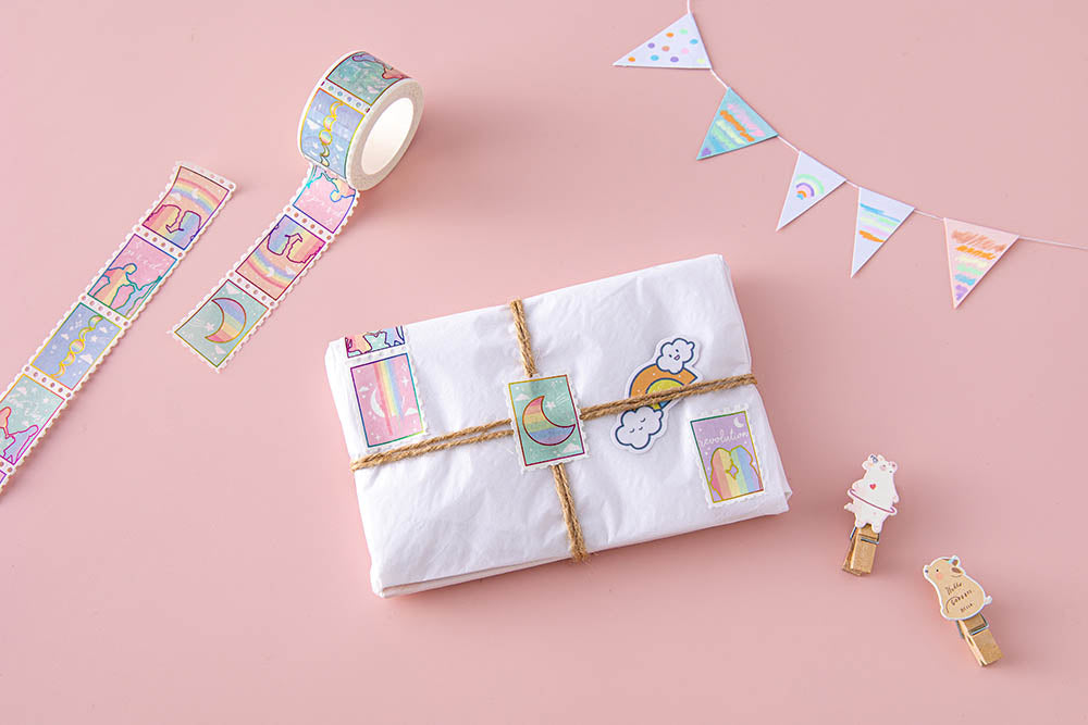 Tsuki Rainbow Pride Washi Tape on small gift wrapped parcel with twine and stickers with bunting and wooden pegs on light pink background