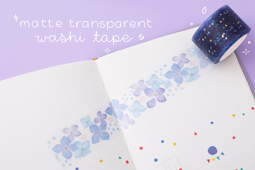 Close up of Tsuki Endless Summer matte transparent washi tape roll with floral design on open bullet journal page on lilac background