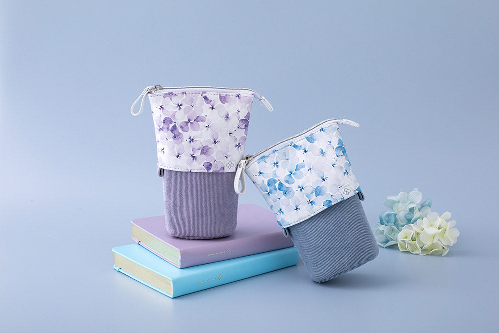 Tsuki Endless Summer Pop-Up pencil case in petal blue held in hands with pens and Tsuki Endless Summer washi tapes on light blue background