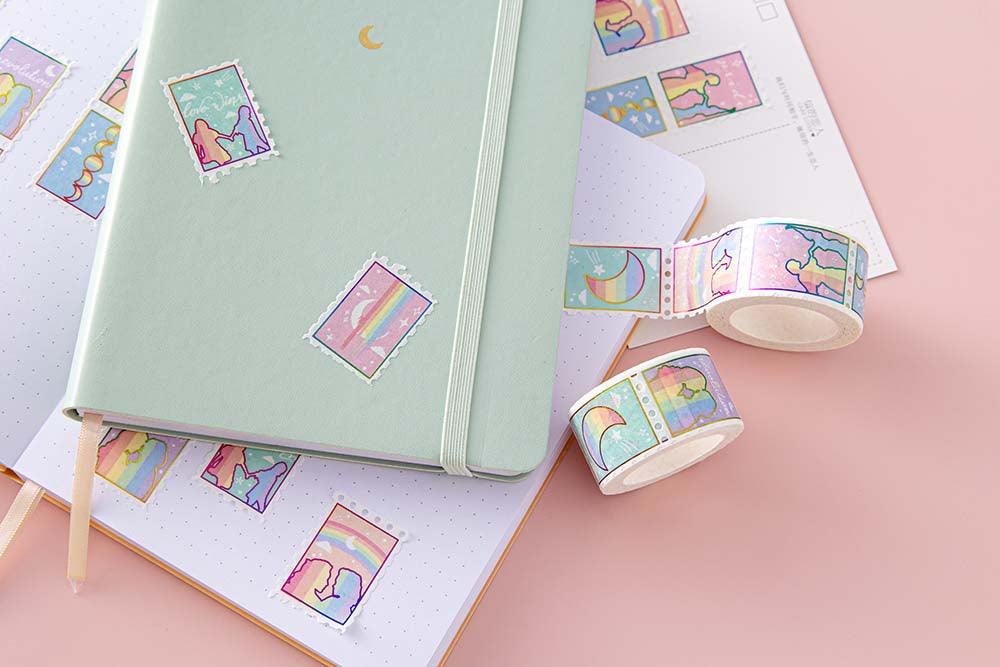 Close up of Tsuki Rainbow Pride Washi Tape on open notebook page with mint matcha Tsuki Pastel Edition Bullet Journal and postcard on light pink background