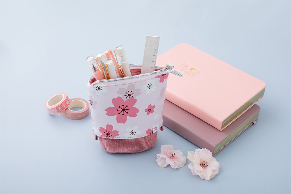 blush pink sakura pop up pencil case with petal pink and blush pink cherry blossom bullet journal notebook in blue background