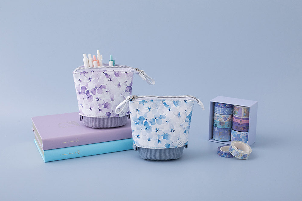 Tsuki Endless Summer Pop-Up pencil cases in petal blue and lilac bloom with pens on stacked Tsuki Endless Summer Bullet journals with Tsuki Endless Summer Washi tape set on light blue background