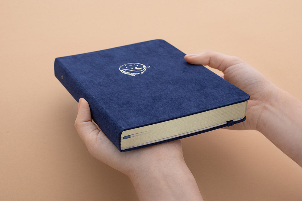 Tsuki soft velvet deep blue Gentle Giant luxury edition notebook with gold edged pages and held in hands at an angle in peach background