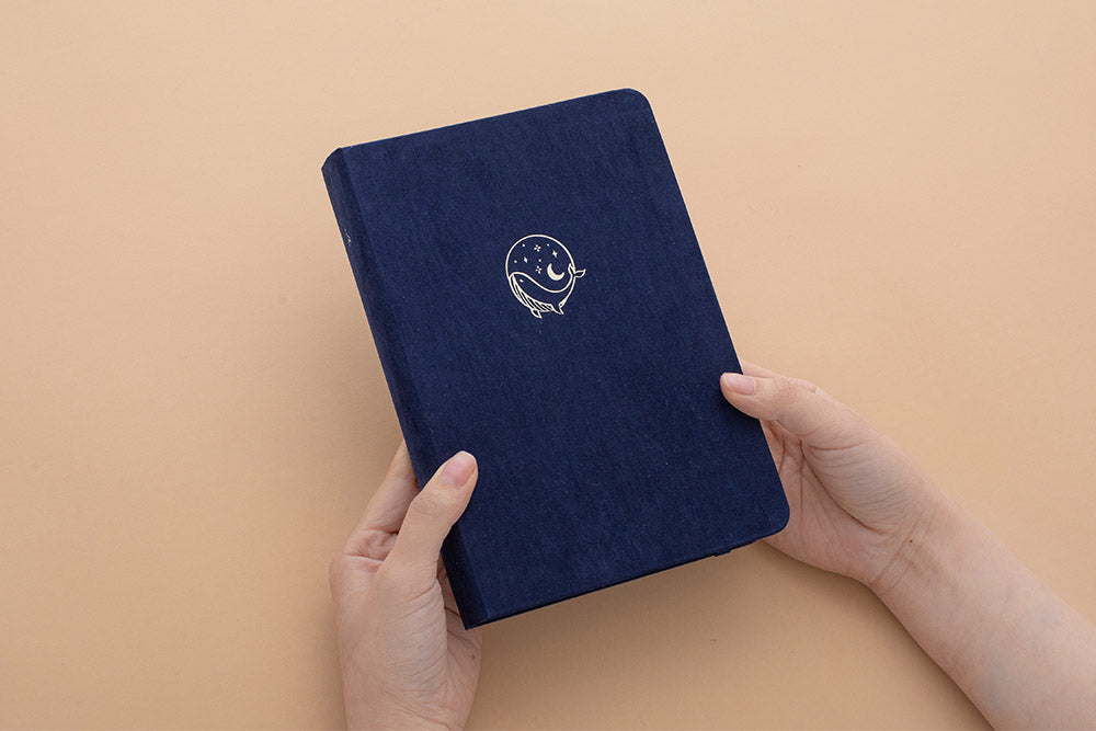 Tsuki soft velvet deep blue Gentle Giant luxury edition notebook held in hands at an angle in peach background