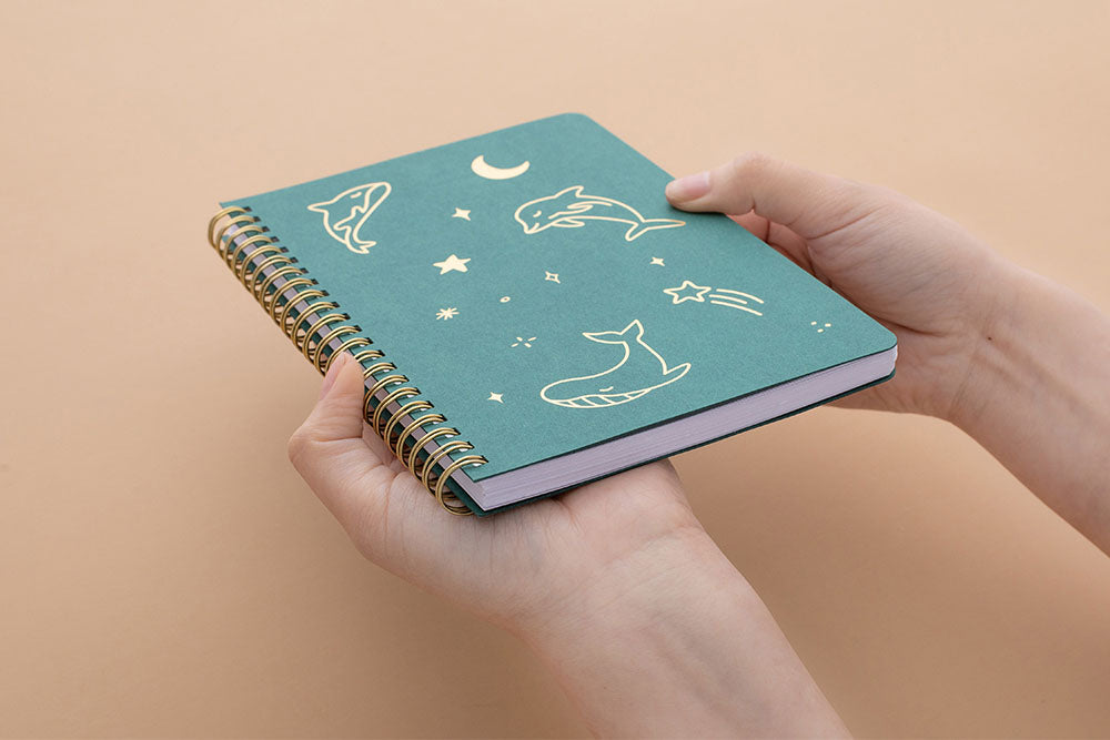 Tsuki Ocean Edition Ring Bound notebook in deep teal held in hands at an angle in peach background