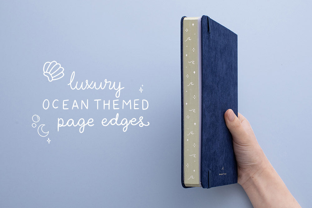 Tsuki deep blue soft velvet Gentle Giant luxury edition notebook held in hand at an angle with luxury ocean themed gold page edges in blue background