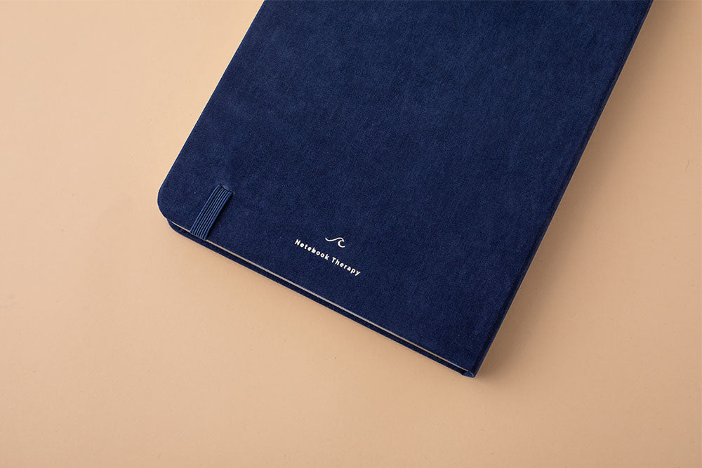 Close up of the back cover of deep blue soft velvet Tsuki Gentle Giant luxury edition bullet journal on peach background
