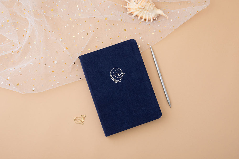 Tsuki soft velvet deep blue Gentle Giant luxury edition notebook with gold pen and seashell on peach background