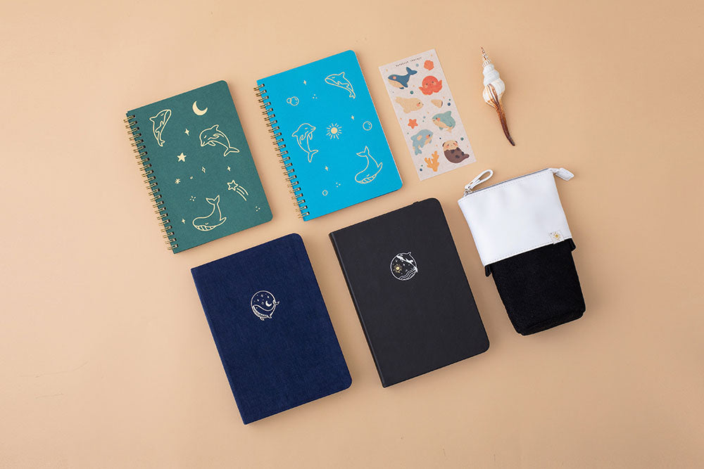 Tsuki deep blue Gentle Giant luxury edition notebook with aqua blue and moss green ocean edition ring bound notebooks and deep black Playful Orca bullet journal and Orca Black Tsuki Ocean pop up standing pencil case and Tsuki Ocean Edition Washi tape with seashell on peach background