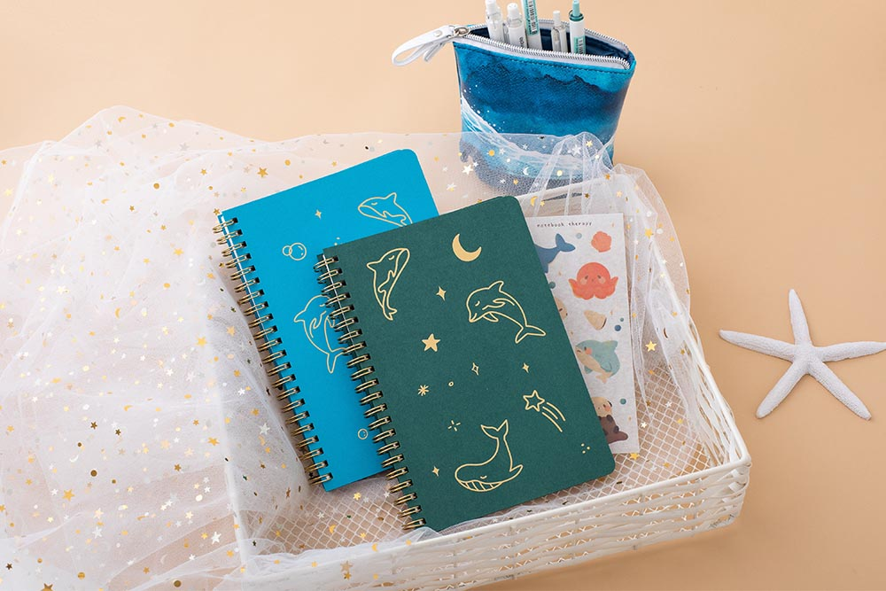 Tsuki Ocean Edition Ring Bound notebooks in aqua blue and deep teal with free sticker sheet and ocean edition pop up standing pencil case in ocean blue in basket with starfish in peach background