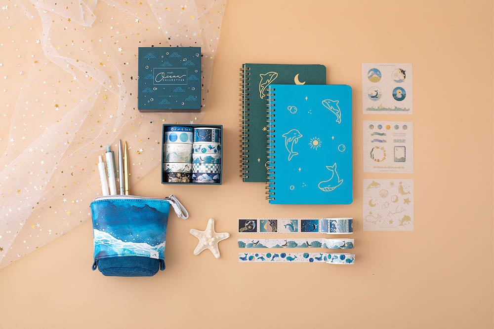Tsuki Ocean Edition Washi Tapes and sticker sheet set with Ocean Edition pop up standing pencil case in Ocean Blue and aqua blue and deep teal ocean edition ring bound notebooks with starfish on peach background