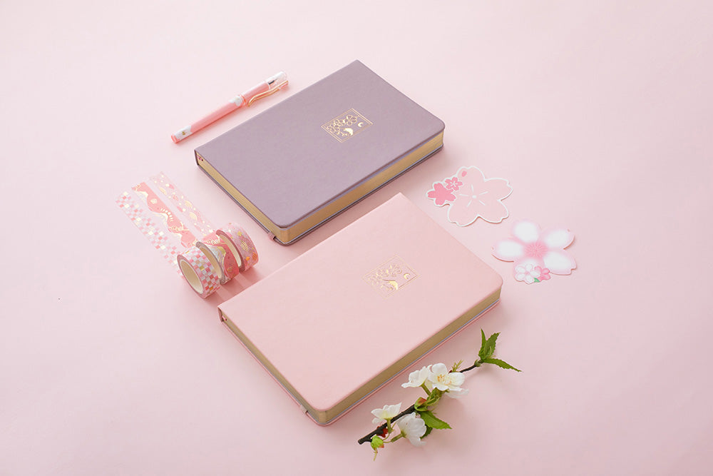 Blush pink and petal pink sakura themed bullet journal notebooks on pink backgrounds with cherry blossom decorations