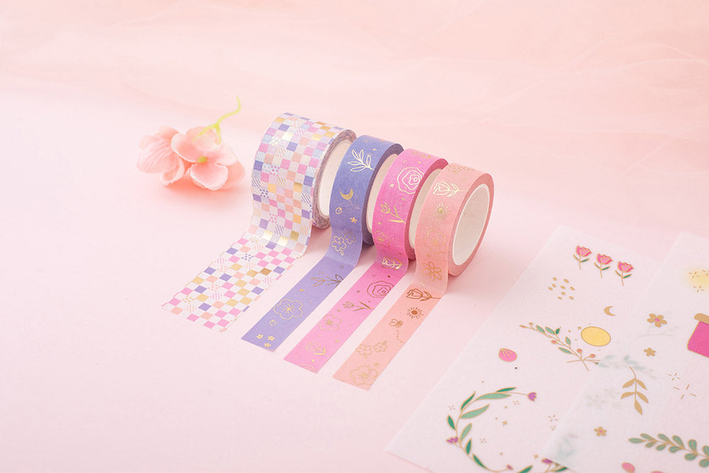 Tsuki Floral collection washi tapes rolled out and sticker sheets laid out on pink background