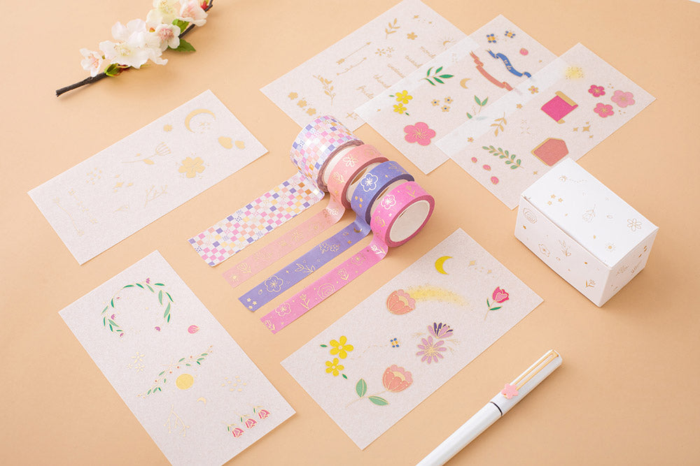 Tsuki Floral washi tapes rolled out with 6 sticker sheets laid out flat on a peach background