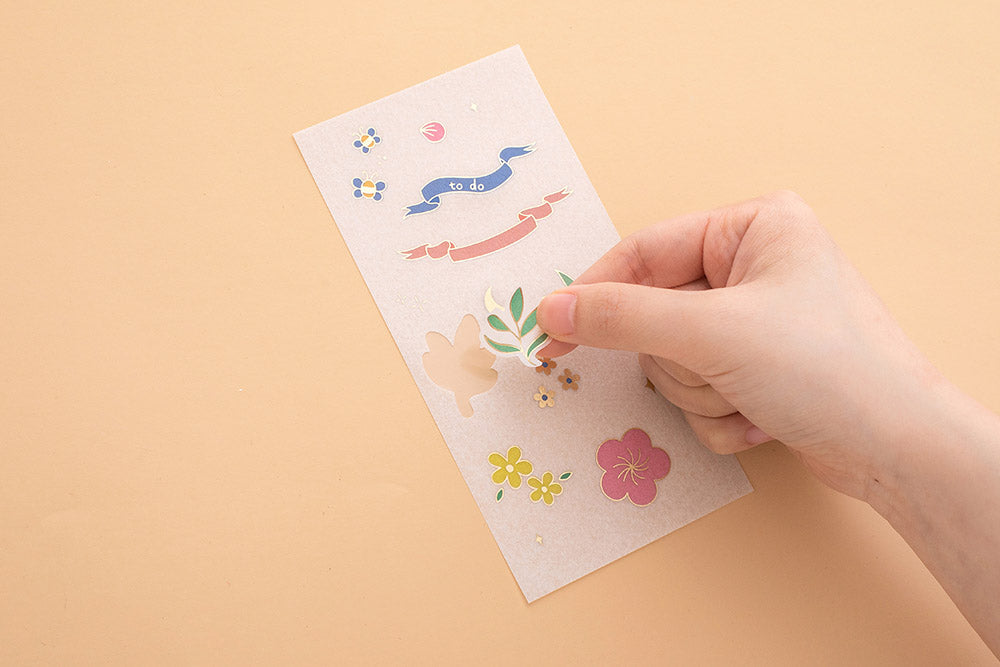 Hand peeling sticker off Tsuki Floral sticker sheet on peach background