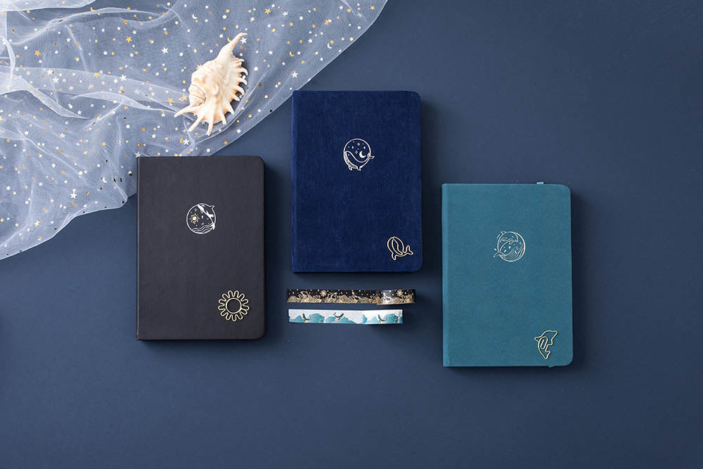 Tsuki deep blue Gentle Giant luxury edition notebook with deep black Playful Orca bullet journal and sea green Dolphin Days notebook and Tsuki Ocean Edition Washi tape with seashell on dark blue background