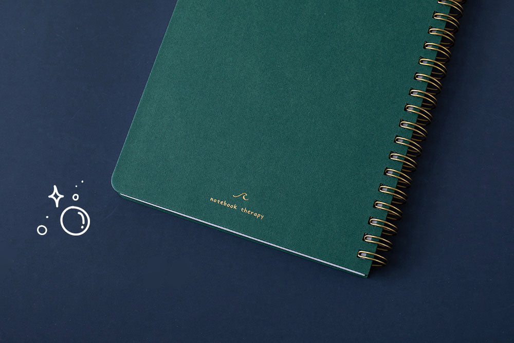 Close up of the back cover of Tsuki Ocean Edition Ring Bound notebook in deep teal on dark blue background