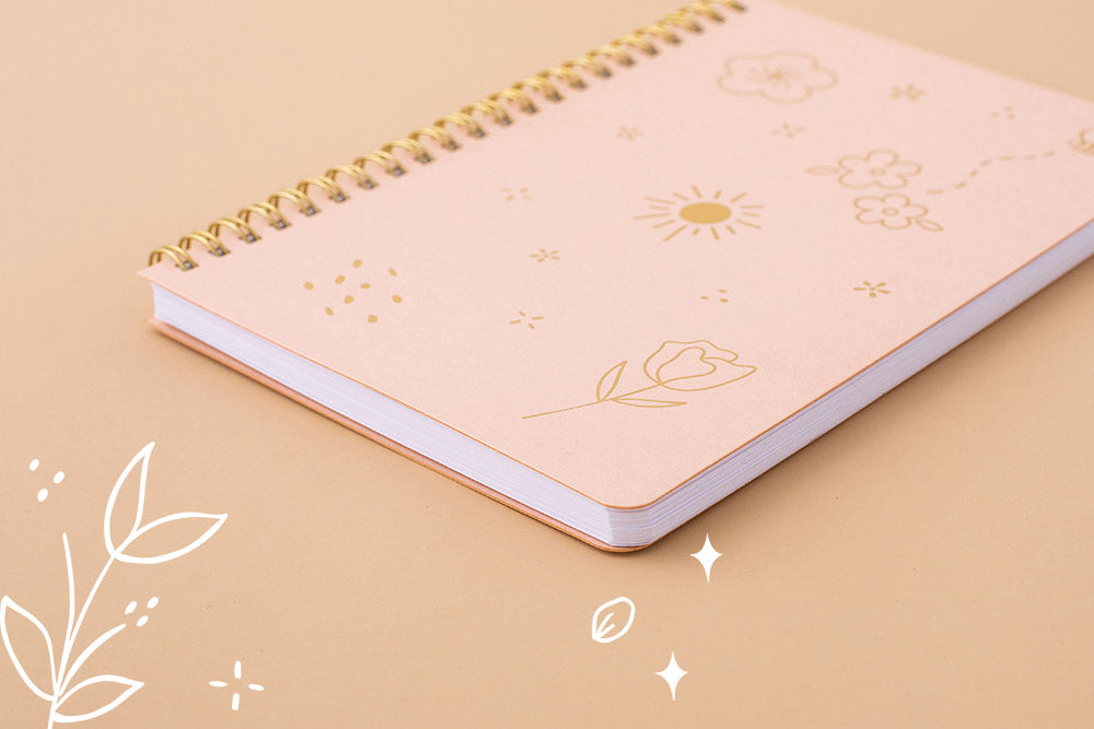 Tsuki Floral honey peach ringbound bujo laid on peach surface at an angle