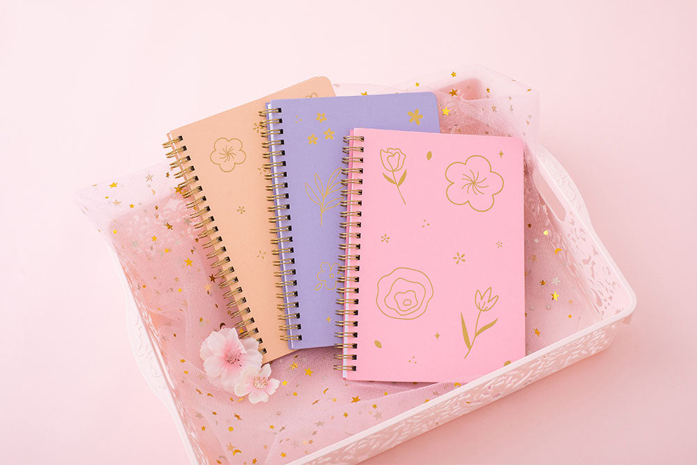 Tsuki Floral collection 3 ringbound bujo laid in pink basket on pink background