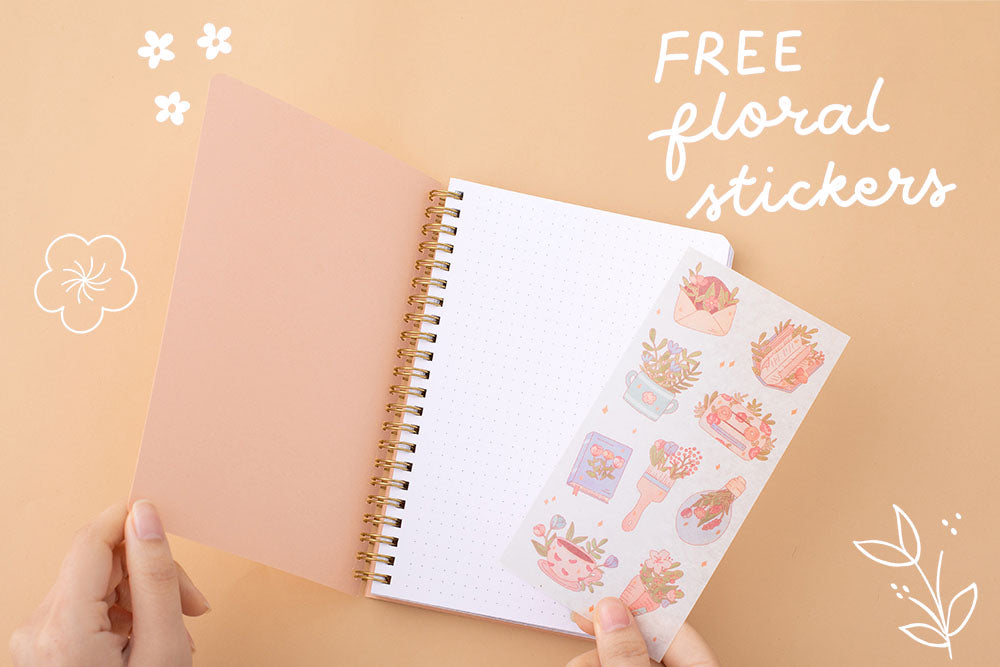 Tsuki Floral honey peach ringbound bujo open page with free sticker sheet held in hand on peach background