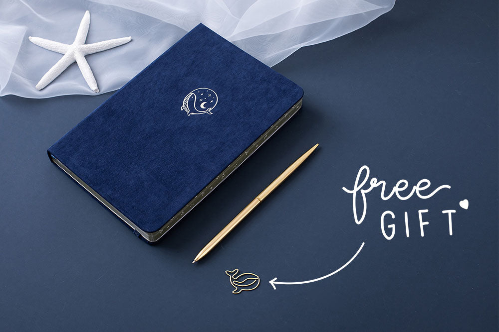 Tsuki deep blue soft velvet Gentle Giant luxury edition notebook at an angle with gold pens and starfish and free whale gift on dark blue background