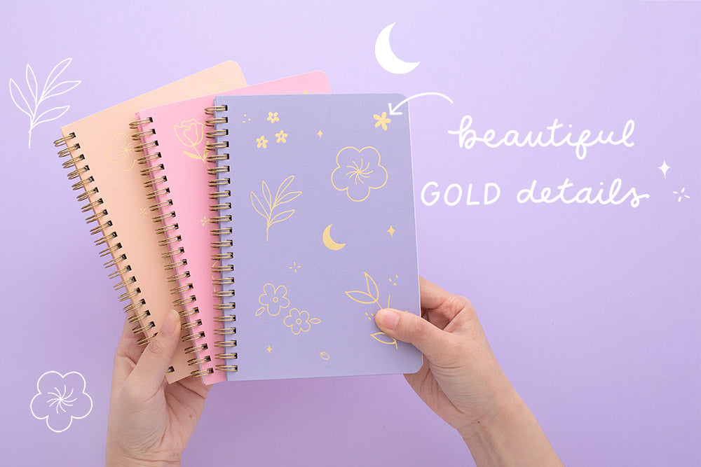 Tsuki Floral collection 3 ringbound bujo held in hands, on lilac background