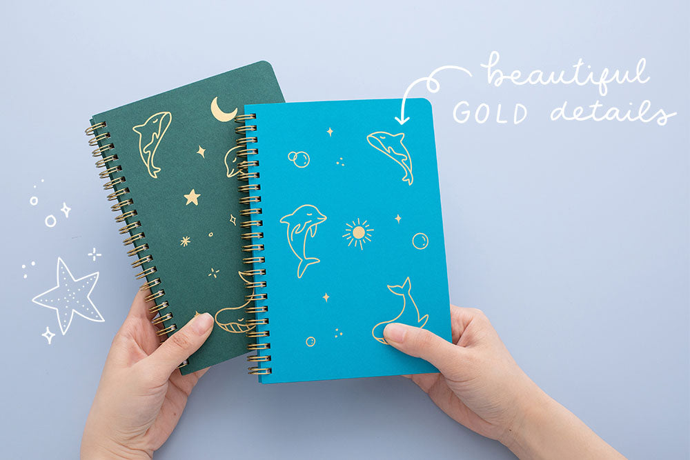 Tsuki Ocean Edition Ring Bound notebooks in aqua blue and deep teal with beautiful gold details held in hands in blue background