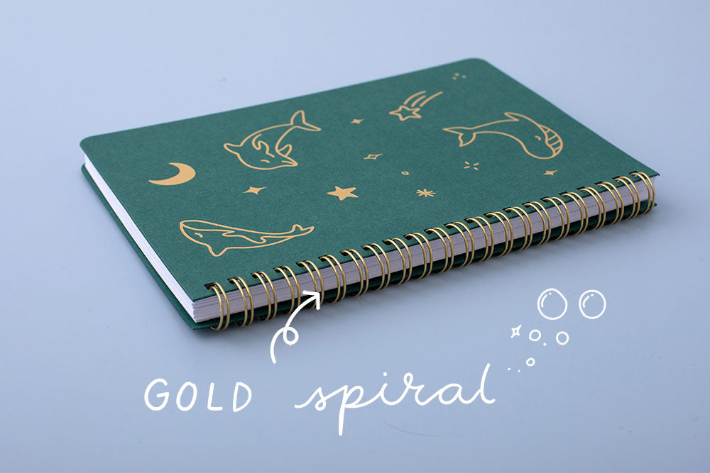 Tsuki Ocean Edition Ring Bound notebook in deep teal with gold spiral spine on blue background