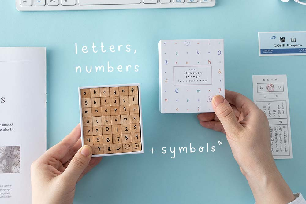 Alphabet Stamps by Notebook Therapy being shown against a blue background. Box open to show letters, numbers, and symbols included in the 42 Alphabet Stamp Set