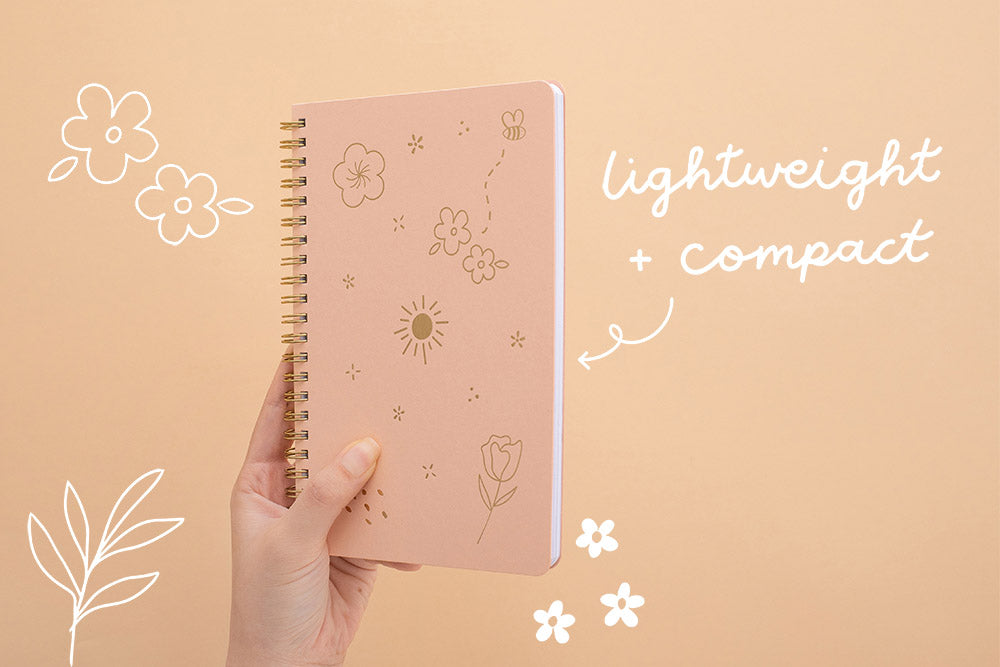 Tsuki Floral honey peach ringbound bujo held in hand on peach background