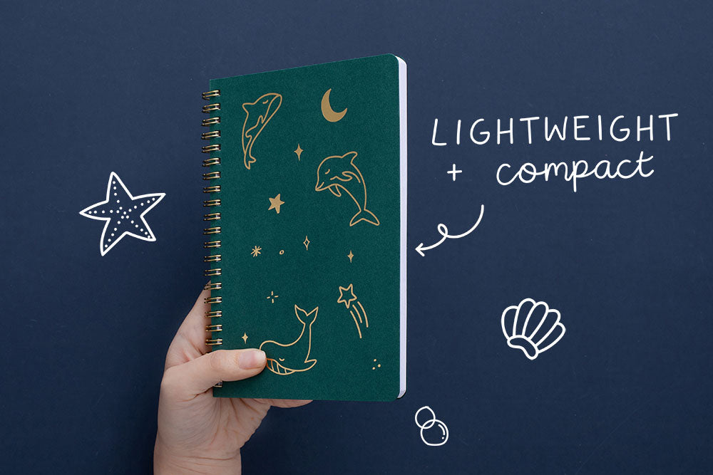 Tsuki Ocean Edition Ring Bound notebook in deep teal with lightweight and compact design held in hand in dark blue background