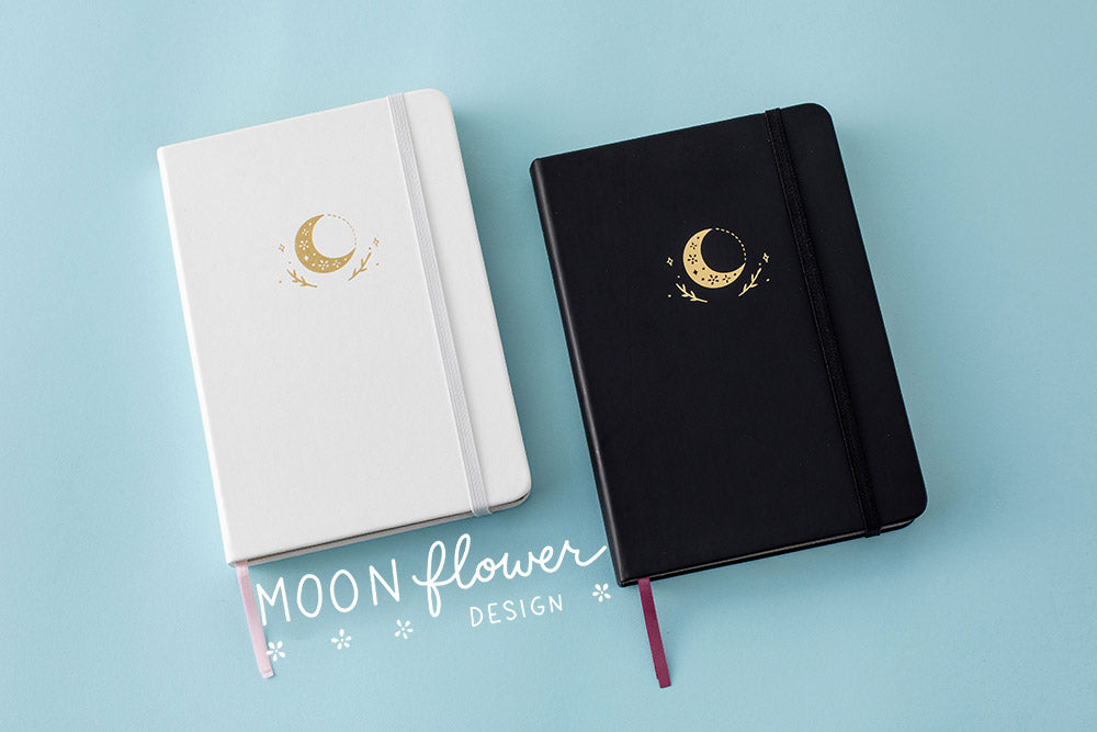 white moon flower bullet journal next to the black moon flower bullet journal