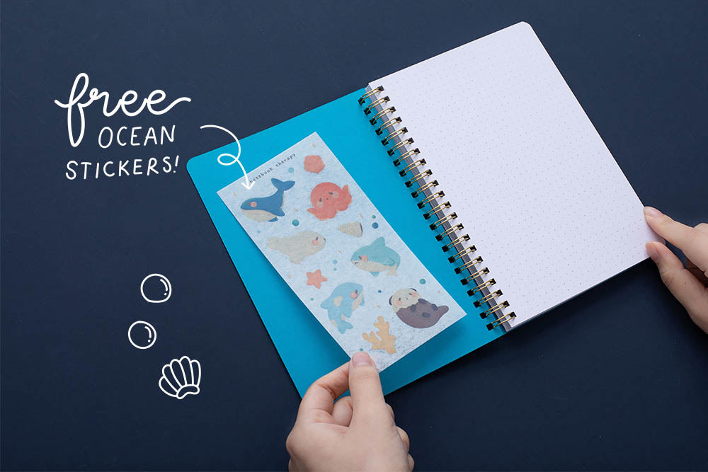 Tsuki Ocean Edition Ring Bound notebook in aqua blue open with free ocean stickers held in hands on dark blue background