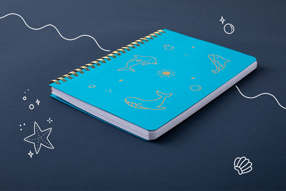 Tsuki Ocean Edition Ring Bound notebook in aqua blue at an angle on dark blue background