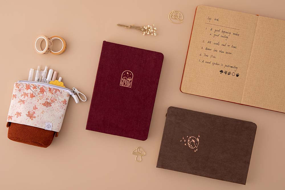 Tsuki Kraft Paper Limited Edition Bullet Journals in Kinoko and Nara with open Kitsune kraft paper notebook with free bookmark gifts and Tsuki 'Maple Dreams' Pop Up Pencil case in maple and Tsuki 'Maple Dreams' Washi Tapes with dried flowers on beige background