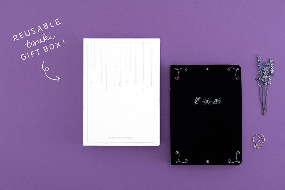 Tsuki 'Moonlit Spell' Limited Edition Holographic Bullet Journal in black with reusable Tsuki gift box with Tsuki 'Moonlit Spell' Washi Tape Set with amethyst stones on purple background