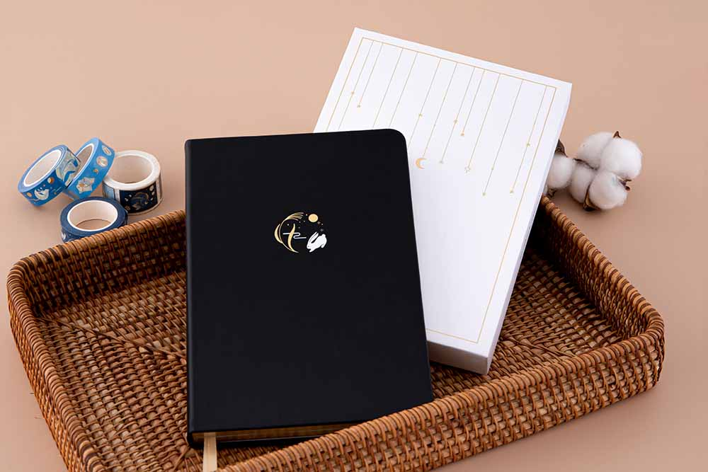Tsuki 'Moonlit Wish' Limited Edition Bullet Journal with luxury gift box packaging in brown basket with Tsuki 'Moonlit Wish' Washi Tapes with cotton flowers on light brown background