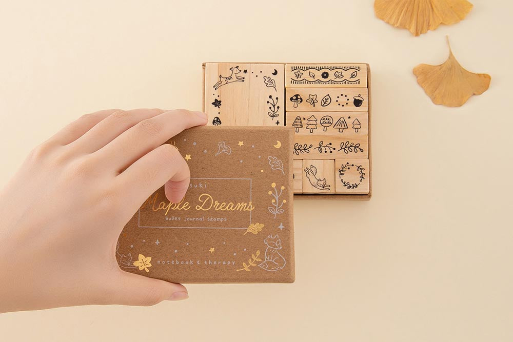 Tsuki 'Maple Dreams' Bullet Journal Stamp Set held in hands with autumn leaves in cream background
