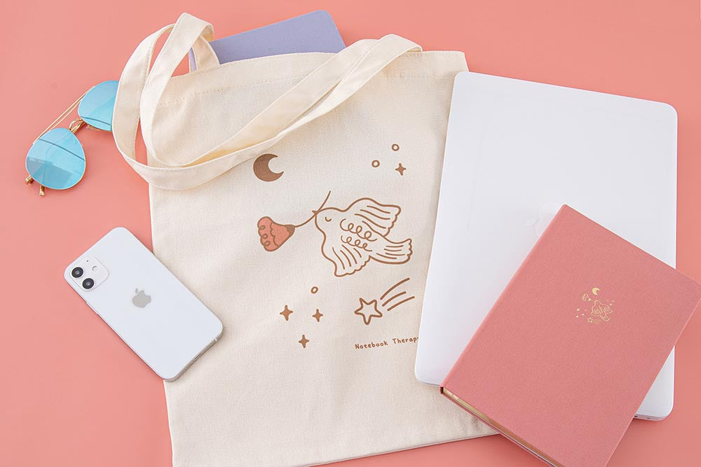 Tsuki 'Moonflower' Limited Edition Tote Bag with 'Full Bloom' Limited Edition Bullet Journal inside with 'Suzume' Limited Edition notebook and laptop and phone and sunglasses on coral pink background