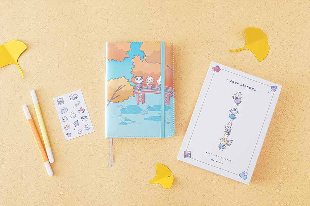 Tsuki 'Four Seasons: Autumn Edition' Bullet Journal made with milkkoyo with eco-friendly gift box and free stickers sheet with pencils and autumn leaves on light brown background