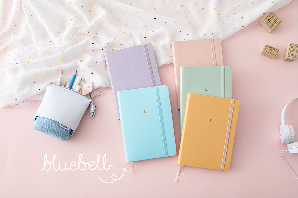 Tsuki Pastel Edition Bullet Journals with netting in mint matcha and pink sakura and lilac taro and honey butter and bluebell with headphones and tsuki pastel pop up pencil case and on light pink background