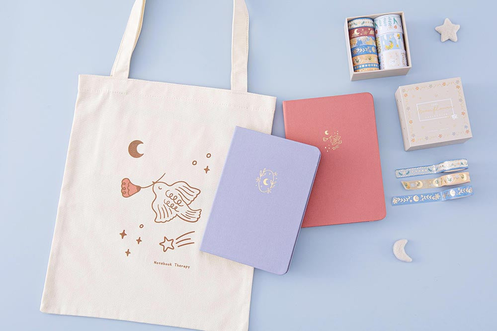 Tsuki Moonflower Collection including 'Suzume' Limited Edition Bullet Journal and 'Full Bloom' Limited Edition Notebook and 'Moonflower' Washi Tape Set and 'Moonflower' Tote Bag with star and moon on light blue background