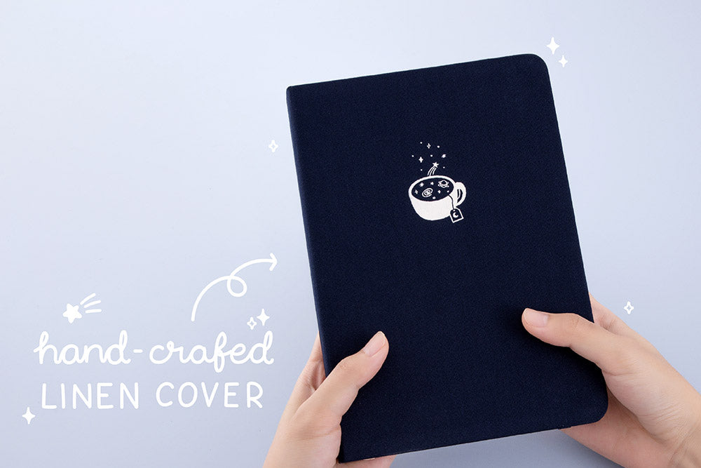 Tsuki 'Cup of Galaxy' Limited Edition Holographic Bullet Journal with handcrafted linen cover held in hands in light blue background