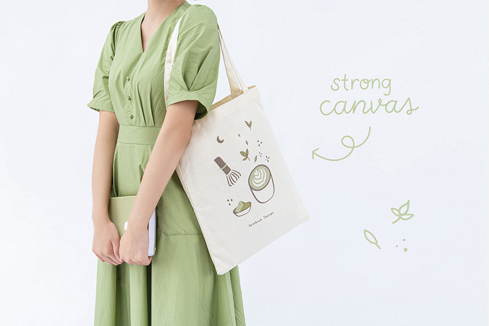 Tsuki 'Matcha Matcha' Tote Bag with strong canvas on model's arm with Tsuki 'Matcha Matcha' Limited Edition Bullet Journal held in arms in light grey background